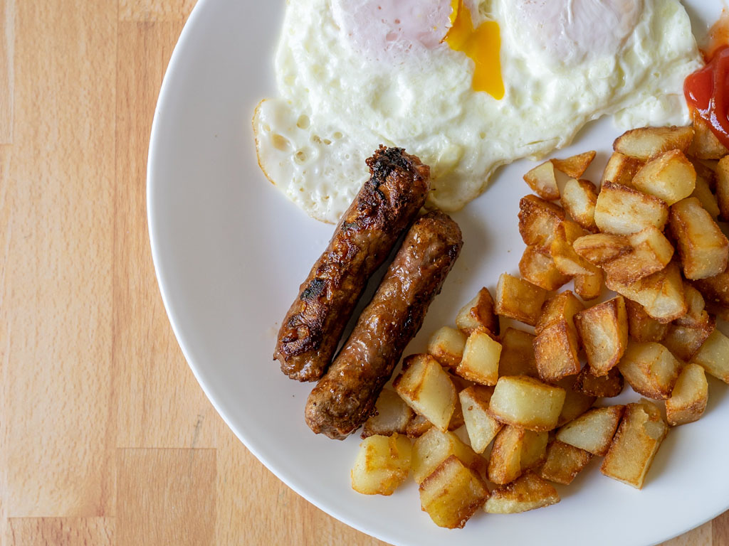 Beyond Breakfast Sausage Links cooked with eggs and breakfast potatoes close up