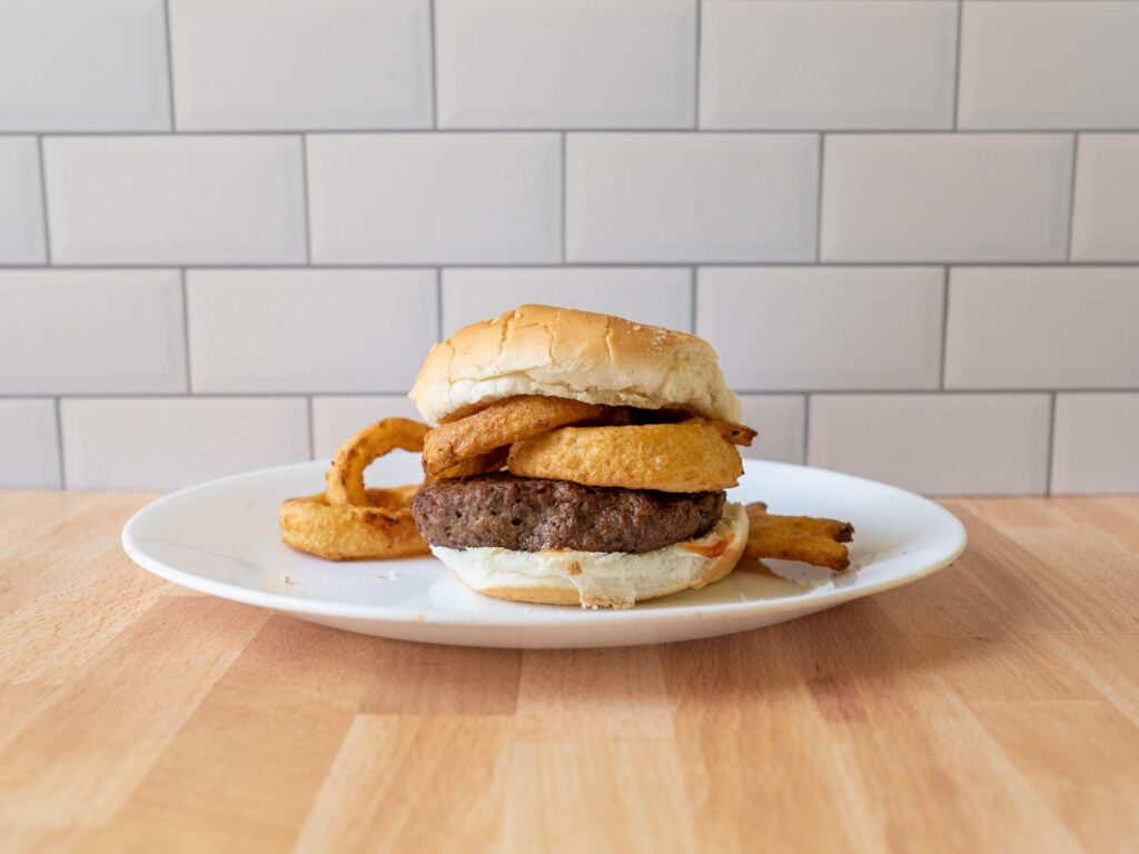 Nathan's Famous Thick Sliced Battered Onion Rings air fried on burger