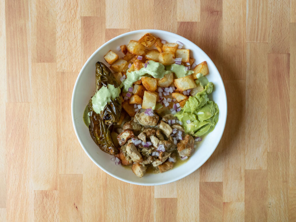 Del Real Foods Pork Chile Verde cooked with Fred potatoes, guacamole and Wild Coyote lime ranch and jalapeno