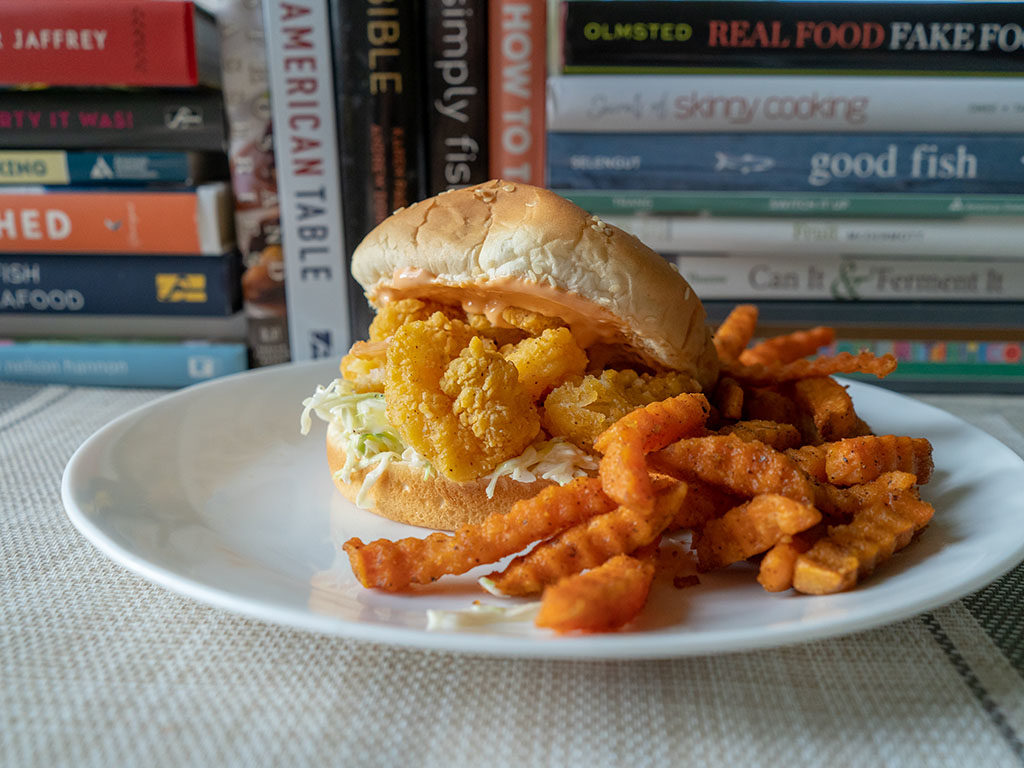 Whole Catch Shrimp Poppers on. bun with sweet potato fries
